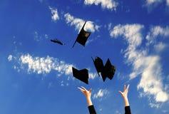 Studente con le congratulazioni che gettano i cappelli di graduazione Fotografia Stock