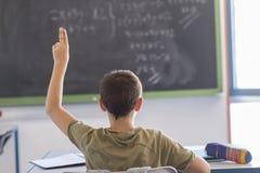 Studente con le mani su in aula durante la lezione Immagine Stock