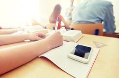 Studente con lo smartphone ed il taccuino alla scuola Fotografia Stock