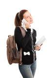 Studente con lo zaino ed il blocco note che parla sul telefono Fotografia Stock
