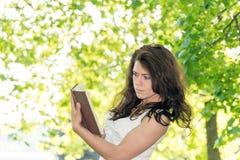 Studente con un libro in parco Immagine Stock Libera da Diritti