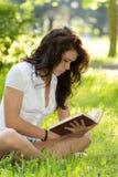 Studente con un libro in parco Immagini Stock Libere da Diritti