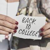 Studente con una nota con il testo di nuovo all'istituto universitario Immagini Stock