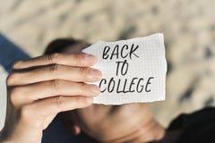 Studente con una nota con il testo di nuovo all'istituto universitario Immagine Stock