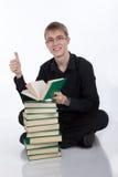 Studente con una pila di libri Immagini Stock