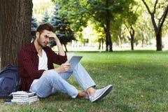 Studente concentrato che prepara per l'esame in parco Immagine Stock Libera da Diritti