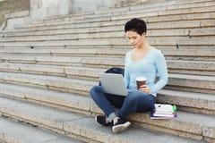 Studente concentrato che si siede sulle scale facendo uso del computer portatile Fotografie Stock