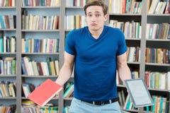 Studente confuso che prova a scegliere fra il libro e Fotografia Stock Libera da Diritti