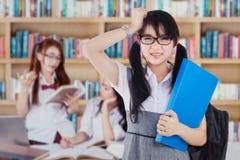 Studente confuso con il gruppo in biblioteca Immagini Stock Libere da Diritti