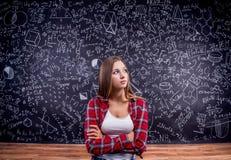 Studente contro una grande lavagna con i simboli matematici Immagini Stock Libere da Diritti