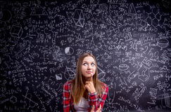 Studente contro una grande lavagna con i simboli matematici Fotografia Stock