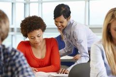 Studente d'aiuto dell'insegnante afroamericano nella classe Fotografie Stock