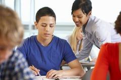 Studente d'aiuto dell'insegnante afroamericano nella classe Immagine Stock