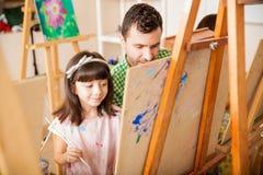 Studente d'aiuto dell'insegnante con la sua pittura Immagine Stock Libera da Diritti