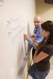 Studente d'aiuto dell'insegnante con un problema per la matematica su una lavagna. Fotografia Stock