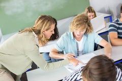 Studente d'aiuto dell'insegnante nella classe Fotografia Stock Libera da Diritti