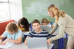Studente d'aiuto dell'insegnante nella classe Immagini Stock Libere da Diritti