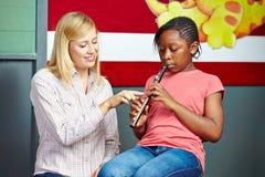Studente d'aiuto dell'insegnante per giocare flauto Immagine Stock Libera da Diritti