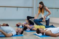 Studente d'aiuto dell'istruttore di yoga con le flessioni della gamba Fotografia Stock