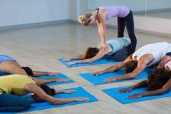 Studente d'aiuto dell'istruttore di yoga con una posa corretta Immagine Stock