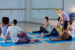 Studente d'aiuto dell'istruttore di yoga con una posa corretta Immagini Stock Libere da Diritti