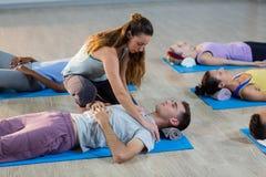 Studente d'aiuto dell'istruttore di yoga con una posa corretta Fotografia Stock Libera da Diritti