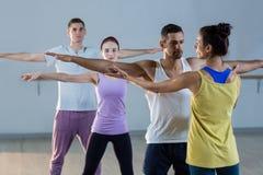 Studente d'aiuto dell'istruttore di yoga con una posa corretta Fotografia Stock