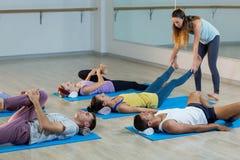 Studente d'aiuto dell'istruttore di yoga con una posa corretta Fotografie Stock Libere da Diritti