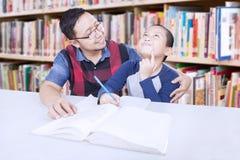 Studente d'istruzione dell'insegnante amichevole in biblioteca Immagini Stock