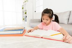 Studente del bambino che esamina manuale scolastico Immagine Stock