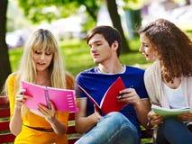Studente del gruppo con il taccuino sul banco all'aperto. Fotografia Stock