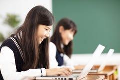 Studente dell'adolescente che impara online con il computer portatile in aula Immagine Stock