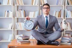 Studente dell'uomo d'affari nella posizione di loto con una sveglia e una a Fotografia Stock Libera da Diritti