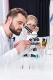 Studente della bambina con gli occhiali che esaminano insegnante che lavora con il microscopio Fotografia Stock Libera da Diritti