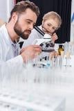 Studente della bambina con gli occhiali che esaminano insegnante che lavora con il microscopio Fotografia Stock