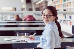 Studente della giovane donna che impara nella biblioteca Fotografia Stock Libera da Diritti