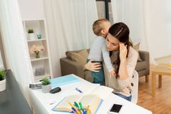 Studente della madre con il bambino che impara a casa Immagine Stock