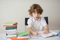 Studente della scuola elementare che si siede ad uno scrittorio che fa compito Immagini Stock