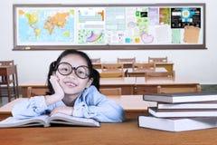Studente della scuola primaria che studia nell'aula Immagini Stock
