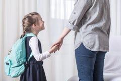 Studente della scuola primaria e del genitore andare di pari passo immagine stock