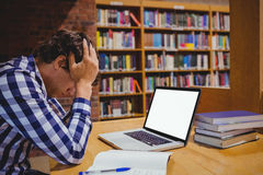 Studente depresso che si siede nella biblioteca con il computer portatile Fotografie Stock Libere da Diritti