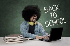 Studente di afro che scrive su un computer portatile Immagini Stock