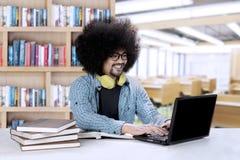 Studente di afro con un computer portatile ed i libri Fotografia Stock Libera da Diritti