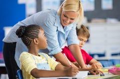 Studente di aiuto dell'insegnante nella classe Fotografia Stock