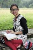Studente di college abbastanza indiano che studia nella città universitaria dell'istituto universitario che indossa abbigliamento Immagini Stock Libere da Diritti