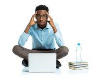 Studente di college afroamericano che si siede con il computer portatile sul bianco Fotografia Stock Libera da Diritti