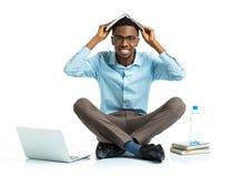 Studente di college afroamericano felice che si siede con il computer portatile e la b Fotografie Stock Libere da Diritti