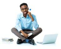 Studente di college afroamericano felice che si siede con il computer portatile, libro Fotografie Stock