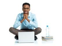 Studente di college afroamericano felice che si siede con il computer portatile sul wh Fotografia Stock