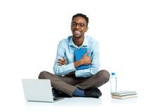 Studente di college afroamericano felice che si siede con il computer portatile sul wh Immagine Stock